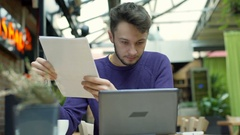 Absorbed man reading papers and checks information on laptop, steadycam shot Stock Footage