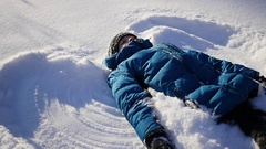 The baby lies on snow and making a snow angel in slowmotion Stock Footage