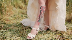 Bride shown a tattoo on her leg under a wedding dress. Surprising view of a Stock Footage