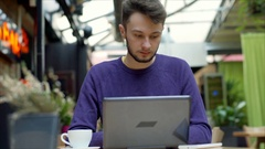 Man receives message on smartphone while typing on laptop, steadycam shot Stock Footage