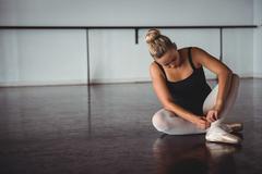Ballerina adjusting stockings while sitting Stock Photos