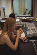 Audio engineer sitting with hands clasped near sound mixer Stock Photos