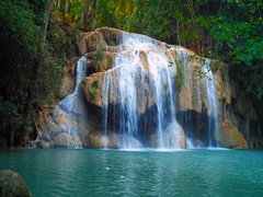 Serene and remote Erawan waterfall in tropical rain forest flows in emerald pond Stock Footage
