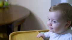Beautiful adorable blonde baby girl with blue eyes sitting on the chair and Stock Footage