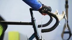 Close-up of  sportsman hands working out on bicycle indoors in the gym. Stock Footage