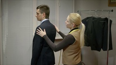 Blonde seamstress measuring a businessman for a suit or in order to alter the Stock Footage