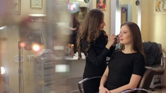 Portrait of beautiful young woman with esthetician making make-up eye shadow. Stock Footage