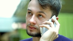 Young man speaking on cellphone and looks absorbed, steadycam shot Stock Footage