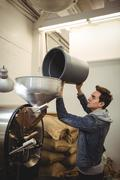 Man putting coffee beans in the coffee roasting machine Stock Photos