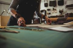 Craftswoman arranging leather piece on work tool in workshop Stock Photos