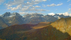 Timelapse of Golden mountain hills, snow tops and red forest. cloud shadows show Stock Footage