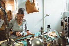 Attentive craftswoman cutting leather Stock Photos