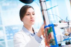 Girl in robotics class research electronic device. Details of the machine with s Kuvituskuvat