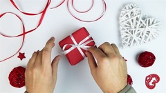 Top view young man unwrapping presents to Valentine's Day at white background Stock Footage
