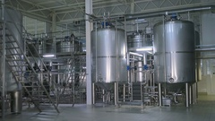 Shiny stainless steel storages, valves and pipes in a modern dairy Stock Footage