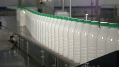 Milk in bottles moving on conveyor. Milk with green caps on a conveyor belt at a Stock Footage