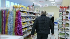 Man buys food at the supermarket, the shelves with goods in the store Stock Footage