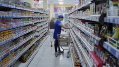 Supermarket employee puts goods on the shelves Stock Footage