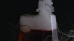 Tilt down on bubbling smoking red champagne flute in macro Stock Footage