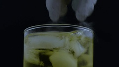 Macro metal tongs stir bubbling beverage hand picks up glass Stock Footage