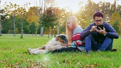Interracial Young couple resting in a park with a dog. Asian man uses tablet, a Stock Footage