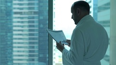 Young man in bathrobe reading documents standing by window at home Stock Footage
