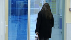 Girl comes out of the supermarket through the automatic door Stock Footage