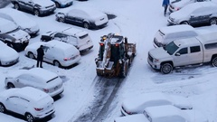 Aerial view of compact tractor with snow plowing equipment cleaning parking lot Stock Footage