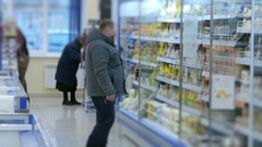 A man chooses food on the supermarket shelf, blurred Stock Footage