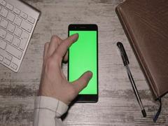 Smartphone On Desk Greenscreen Stock Footage