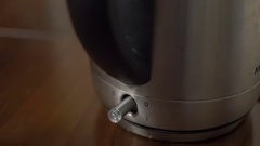 Close up of a hand pressing the clear plastic switch of a silver kettle on a Stock Footage