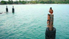 Asian kids jumping from high-board to turquoise water in lagoon Stock Footage