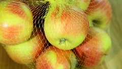 Riped apples in shop packaging on wooden brown background Stock Footage