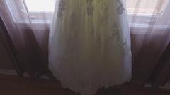 Upwards pan of a beautiful bridal dress hanging in window Stock Footage