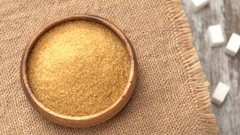 Tabletop of brown sugar rotating on burlap. Four lumps of white sugar on rustic Stock Footage