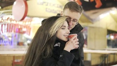 Happy attractive couple drinking tea in a christmas market at night. Beautiful Stock Footage