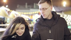 Young couple walk togerher near christmas lights at christmas market with a cup Stock Footage