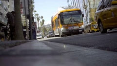 Low view of Hollywood Blvd cars driving down street at dutch angle curb LA Stock Footage