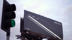 Ad for iPhone 7 on billboard with green traffic light and bird flying away Stock Footage