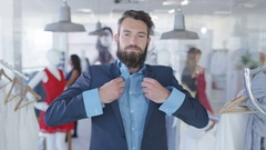 4K Male customer trying on suit & looking into mirror in fashion clothing store Stock Footage