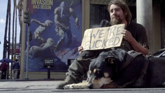 Man sitting on sidewalk with were fucked sign homeless with dog on corner LA Stock Footage