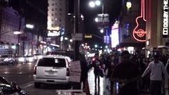 People walking down Hollywood Boulevard Walk of Fame girl stumbling Halloween LA Stock Footage