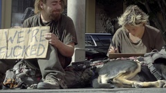 Homeless couple writing signs with dog squatting on street we're fucked sign Stock Footage