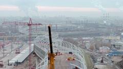 Close aerial shot of big modern truck crane working on huge viaduct or bridge at Stock Footage