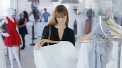 4K Customer holding up garment & looking into mirror in fashion clothing store Stock Footage