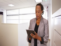 A black businesswoman using a tablet turns to the camera and says hello Stock Footage
