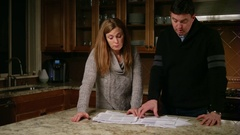 Husband and wife looking at bills in the kitchen, stressed and frustrated Stock Footage