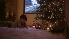 Little boy putting together train tracks in front of the christmas tree Stock Footage