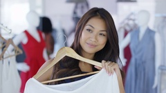 4K Customer in clothing store looking into mirror & taking photo with smartphone Stock Footage