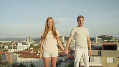 CLOSE UP: Happy boy and smiling girl standing on rooftop raising hands in sky Stock Footage